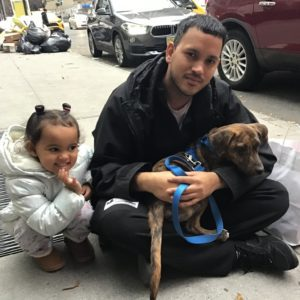 Sofia and Bernardo Rodriguez sit outside the ASPCA's NYC Adoption Center with their just-adopted four-month old puppy, Sorrento