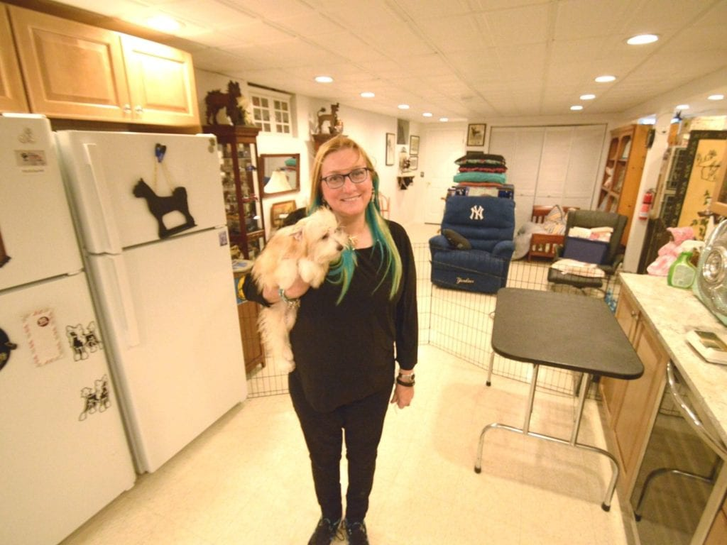 Arlene Butterklee stands in her basement holding a powderpuff Chinese Crested puppy. Photo by Adam Aslan